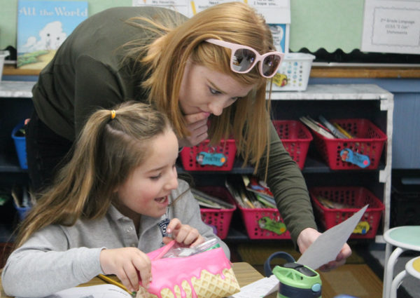First grade student getting help from the teachers aide