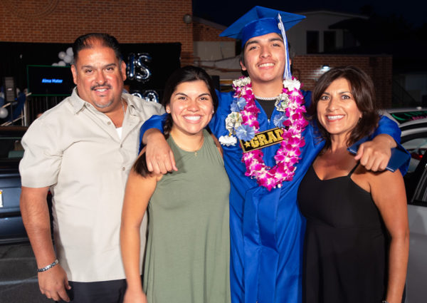 Grad posing with his family