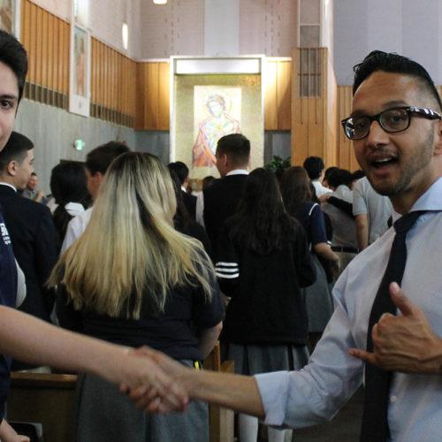 Teachers at Assumption Mass shaking hands