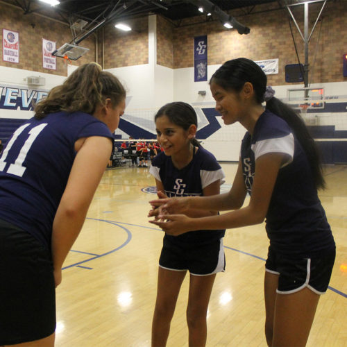 Girls volleyball players discussing their plan